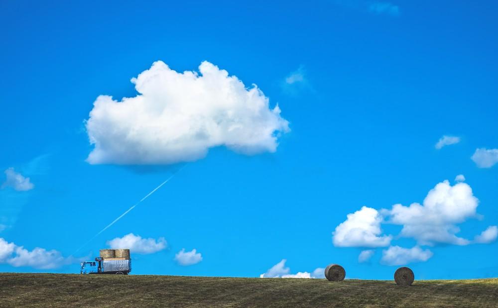 青空の下家畜のエサとなるほし草を丸めて保管できるようにしている牧場
