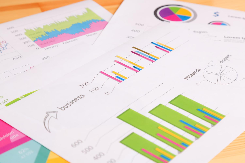 あらゆる数値をグラフ化して分析を試みた資料がたくさん散らばるデスク