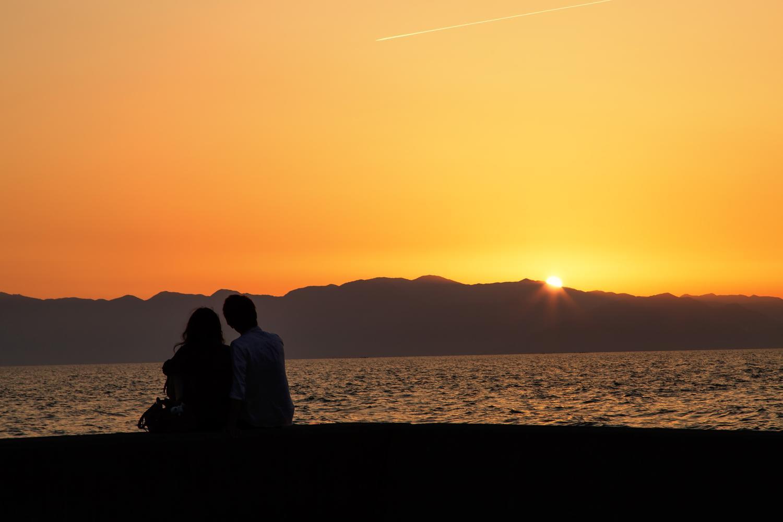 一生そばにいることを誓い合ったカップルが夕日を眺めている