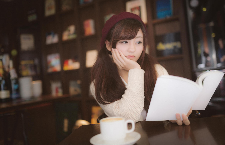 言葉の意味を本で調べてうーんとうなっているかわいい女の子