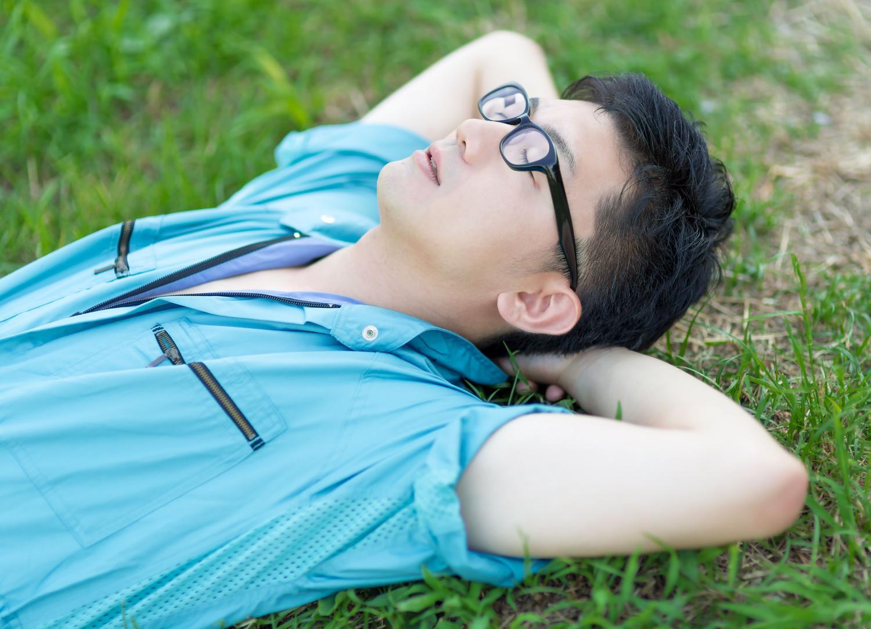 野原で寝そべりながら生きる意味を考える男性