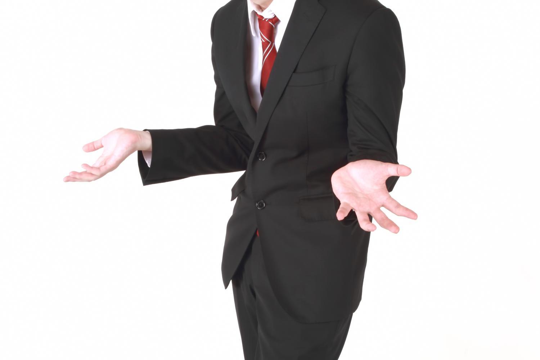 スーツを着た男が両手を広げて開き直りながら言い訳している姿