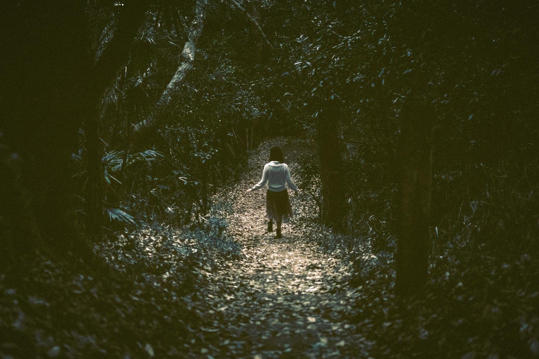 薄暗い森の中のけもの道を一人で歩く少女