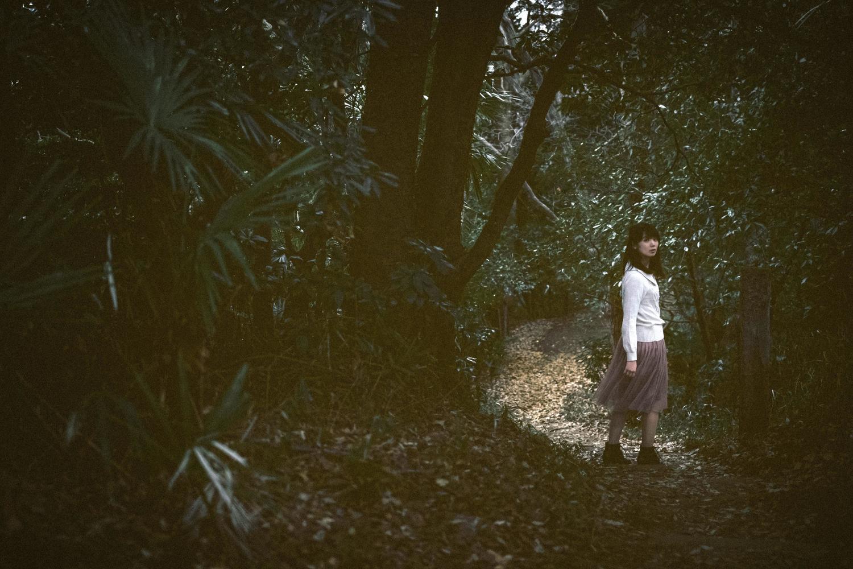薄暗い森の中にいる綺麗な女性