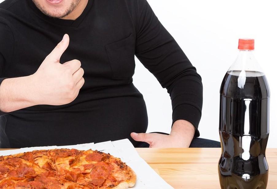 ピザとコーラのゴールデンコンビを前に一人パーティを始めるグッドサインを出している男性
