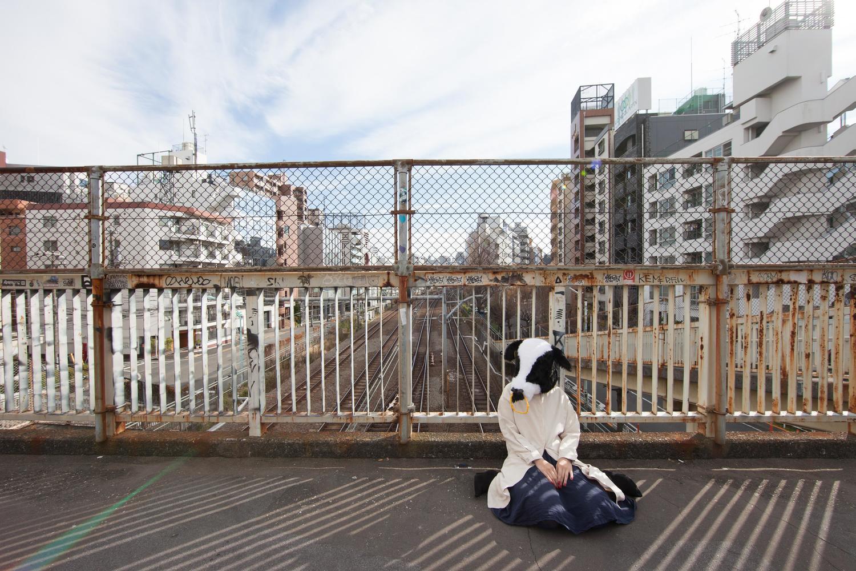 陸橋に座り込む牛の被り物をしている女の子
