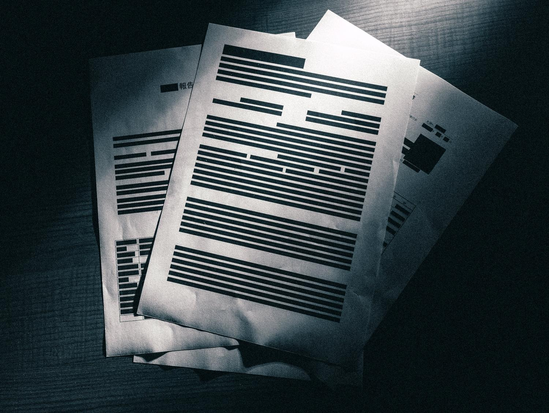 暗闇の中に置かれた黒塗りされた重要書類