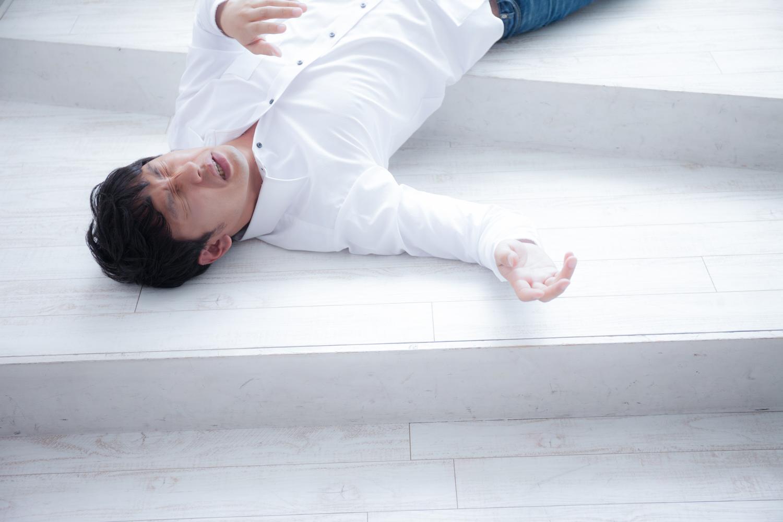 階段で倒れ込み苦悶の表情をうかべる男性