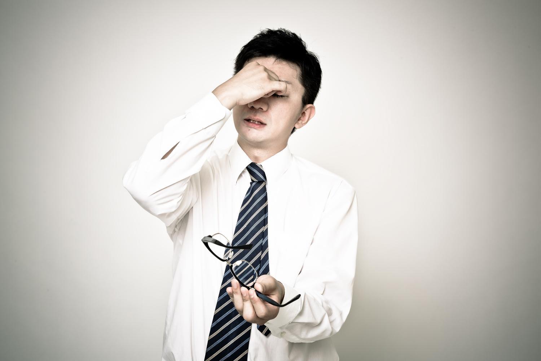 「うわぁやっちまった」と後悔しながら目頭を押さえる復職失敗男性社員
