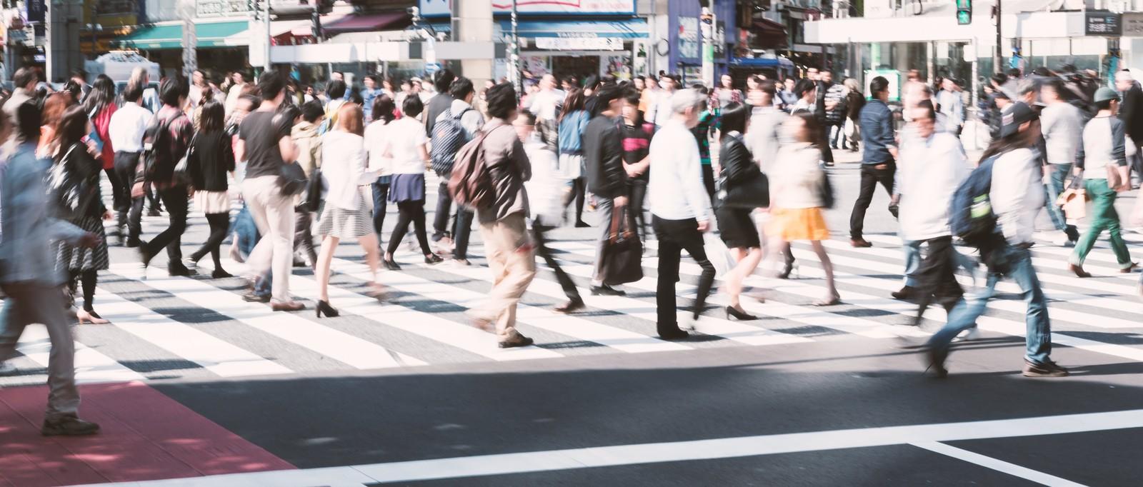 たくさんの人が小走りに行き来する都会の横断歩道
