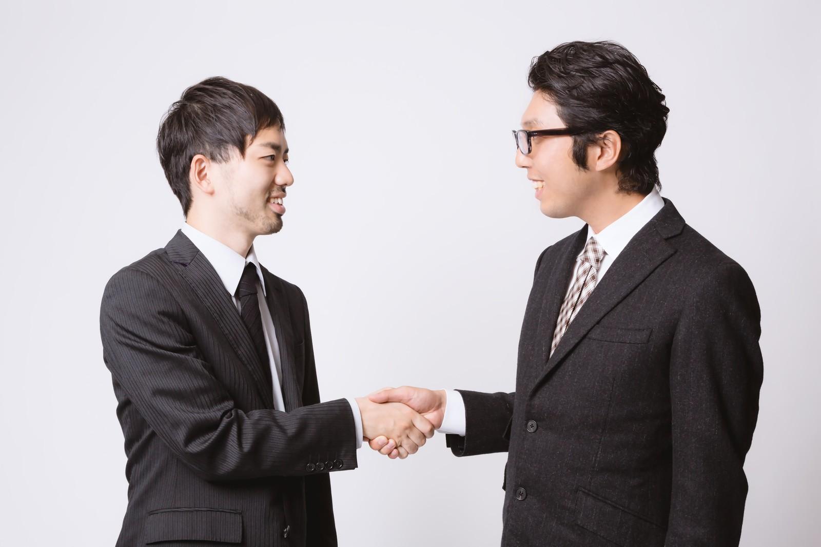 意思の疎通ができて握手をする部下と上司