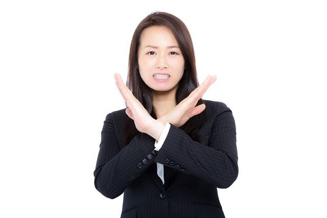 腕を体の前で×にして会社に行きたくないと意思表示するビジネスウーマン