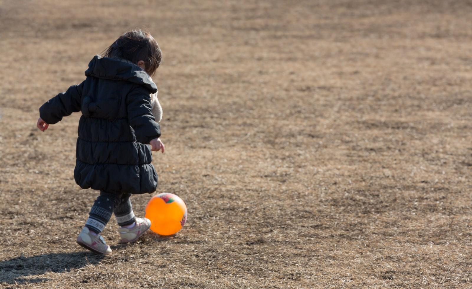 公園内で一人でボールを蹴っているちょっと寂しげな女の子の後ろ姿