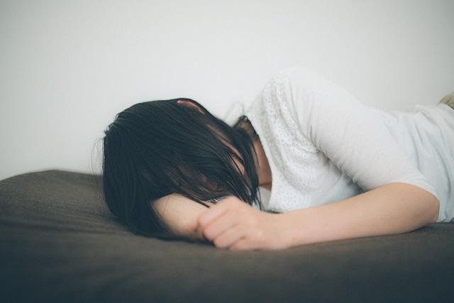 全然眠れなく苦しみながらベッドの上で頭を抱える女性