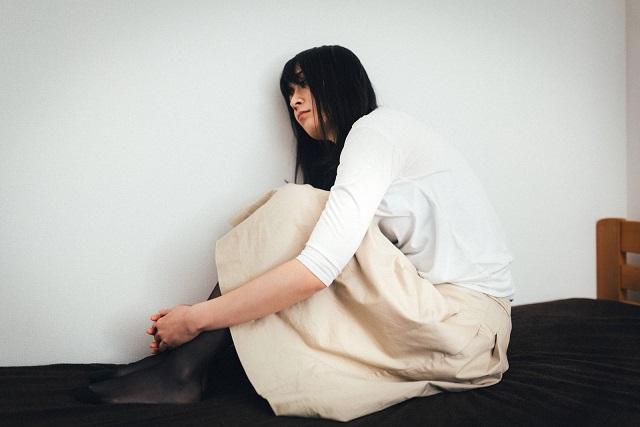 十分な睡眠がとれずに青白い顔しながらベッドの上で体育座りでぼーっとする女性